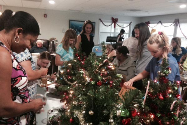 Children and volunteers help decorate for Christmas